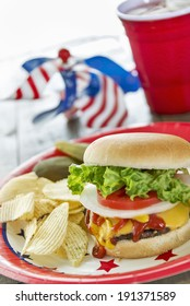 Loaded cheeseburger at a patriotic themed BBQ.  Served with potato chips, pickles and ice tea.