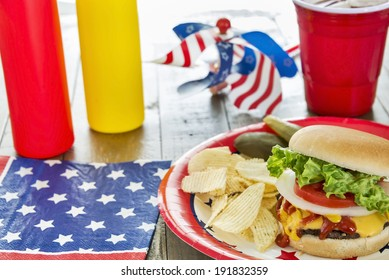 Loaded cheeseburger with potato chips, pickles and ice tea at a patriotic themed cookout