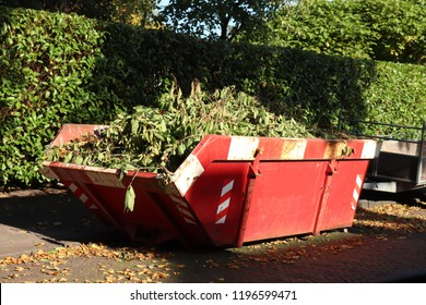 Loaded dumpster or disposal bin loaded with garden rubbish