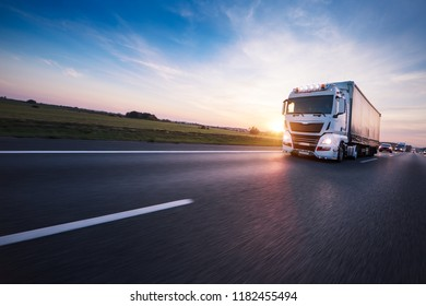 Loaded European truck on motorway in beautiful sunset light. On the road transportation and cargo. - Shutterstock ID 1182455494