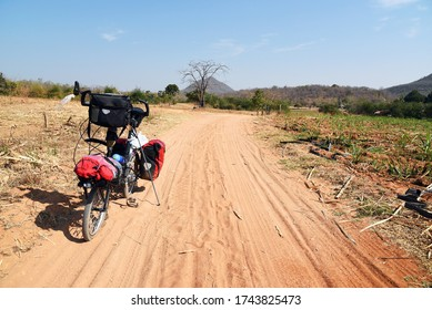 Loaded folding bicycle standing on a sandy road