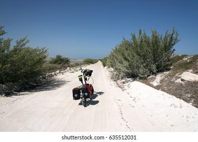 Loaded folding bike at sandy road National Park Rio Lagartos,Mexico