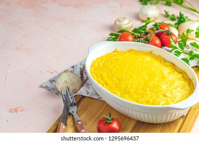 Loaded gratin, julienne or casserole from baked mushroom with chicken and cheese in bechamel sause, white ceramic dish, shallow depth of the field, copy space for you text.