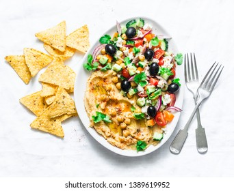 Loaded Greek salad hummus with corn tortilla chips on light background, top view. Delicious appetizer, tapas in a mediterranean style
