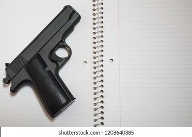Loaded Handgun on School Notebook