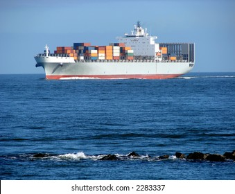 Loaded ocean going container ship with cargo on deck approaching rock bank at  sea