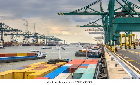 Loaded ships in busy port of Antwerp at container terminal with automated cranes and lots of vessels. Belgium
