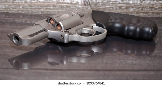 A loaded, stainless steel .357 magnum revolver on a reflective surface with a wooden background