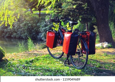 Loaded touring bicycle parking on the nature front of lake with red panniers at sunny day