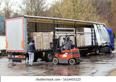 Loaded truck unloading on a harsh rainy day. The trailer is filled with cardboard goods wrapped on pallets. A forklift is moving while approaching it and the trucker is navigating it on a rainy day.