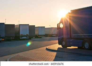 Loaded trucks parked in waiting area on border crossing. Evening view of International hard transportation and logistics with lens flare.