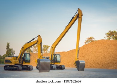 Loader backhoe,excavator digging a trench,Yellow backhoe excavator.Backhoe used in construction, Big excavator on new construction site on sunset sky background and among piles of rock and soil.