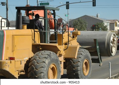 Loader delivering cement pipe for installation in street