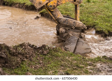The loader is digging in the water