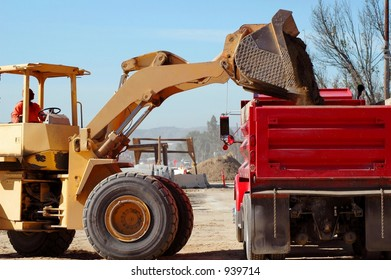 Loader dumping into red truck