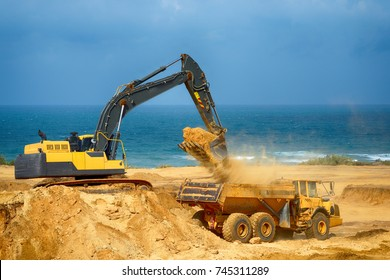 Loader excavator loads the ground in the truck at the road construction