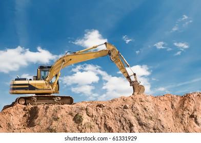 loader excavator in open sand mine over scenic blue sky