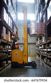 Loader lifting packed goods on shelf of storehouse