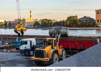 A loader loads granite rubble into a dump truck trailer. The port crane pours granite rubble into a self-propelled barge. Cargo ship carrying bulk materials moored to the pier.