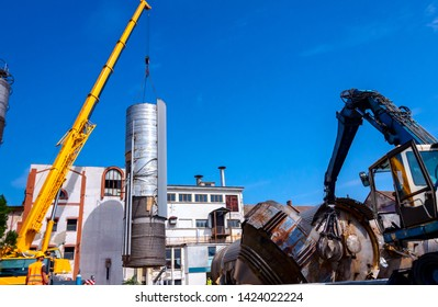 Loader machine with hydraulic grappling claw and crane are bringing down heavy metal silo in industrial complex.