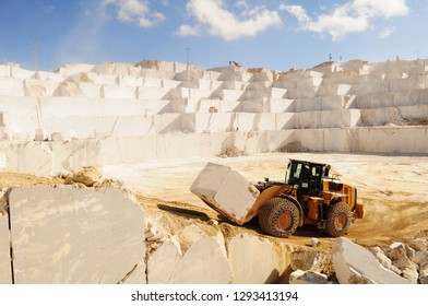 A loader working in marble quarry. Loader carrying marble block
