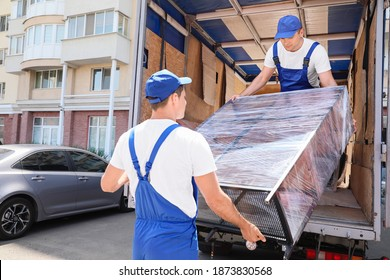 Loaders taking furniture from truck