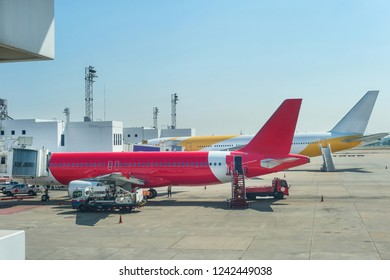 Loading airplanes with gangways and luggage carrying cars at runway of airport