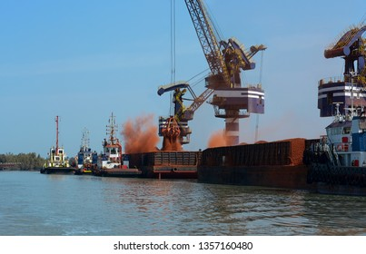 Loading bauxite ore on cargo ship with crane and bucket. Shipment from an storage outside area to a large cargo barge. Grapple crane fill ore into cargo ship.