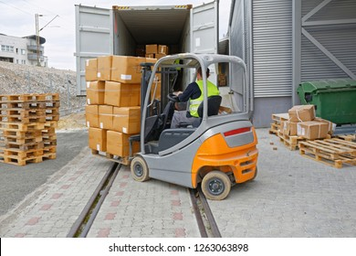 Loading Boxes at Pallet With Forklift in Cargo Container Train