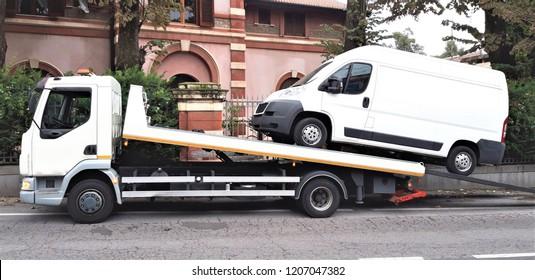 Loading broken minibus on a tow truck on city street