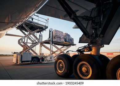 Loading of cargo containers to plane at airport. Ground handling preparing freight airplane before flight.