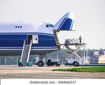 Loading cargo into the cargo plane through the bow. Handling of cargo aircraft at the airport.