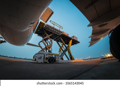 loading cargo outside cargo plane with twilight sky