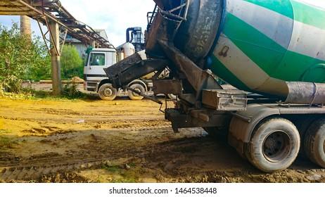 loading cement into a concrete mixer.  Car concrete mixer while loading concrete into concrete mixer