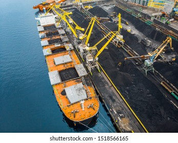 Loading coal anthracite mining in port on cargo tanker ship with crane bucket of train. Aerial top view.