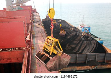 Loading coal from cargo barges onto a bulk carrier using ship cranes and grabs at the port of Samarinda, Indonesia. Close-up view of the work of bulldozers and loaders.