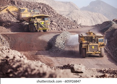 Loading of copper ore on very big dump-body truck and watering road tanker