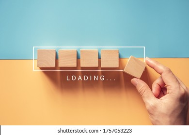 Loading, hand putting wood cube in progress bar.