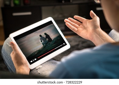 Loading icon rolling on video in an online movie streaming service. Bad and slow internet connection. Film player stopped. Frustrated and confused man watching and holding tablet while spreading arms.
