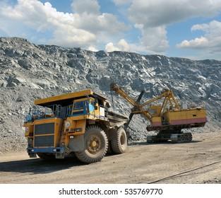 Loading of iron ore on very big dump-body truck