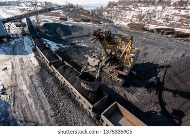 loading of iron ore from a warehouse into a railway dump truck with an excavator. Mining iron ore mining.