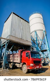 Loading a large red truck with cement