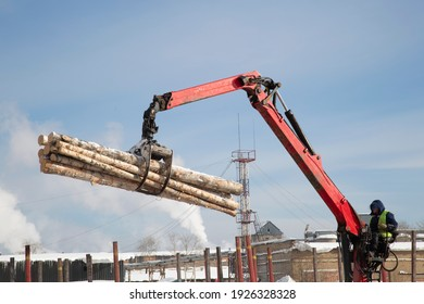 Loading logs on a logging truck. Wood loader. Woodworking industry.