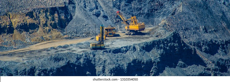 loading of mined iron ore in a pit to excavators in a cargo diesel dump truck.Summer season. Web banner.