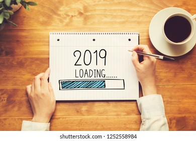Loading new year 2019 with a person holding a pen on a wooden desk