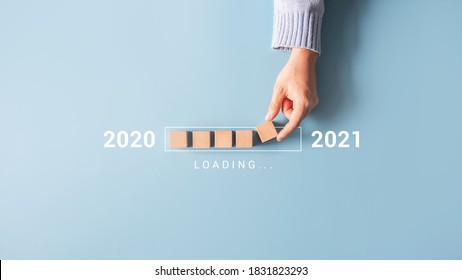 Loading new year 2020 to 2021 with hand putting wood cube in progress bar. - Shutterstock ID 1831823293