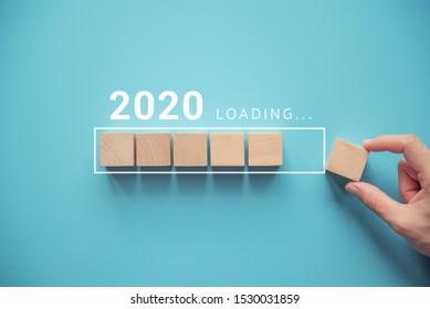 Das neue Jahr 2020 wird mit der Hand geladen, die den Holzwürfel in die Werkstatt bringt.