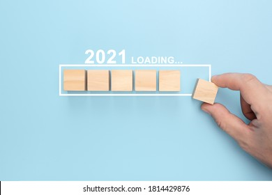 Loading new year 2021 with hand putting wood cube in progress bar. creative background for the new year. Loading new year 2021 concept