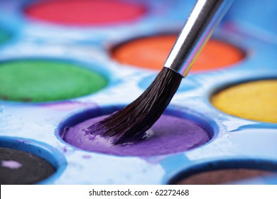 Loading paint brush with paint from a watercolors palette