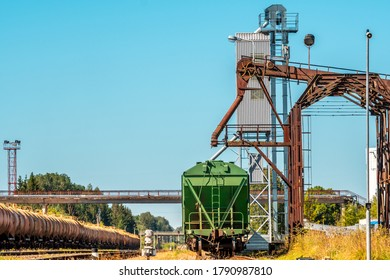 Loading railway wagon standing near the elevator in agriculture zone. Grain silo, warehouse or depository is an important part of harvesting.